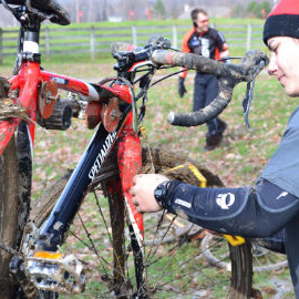 Image of racer working on very dirty cyclocross bike clamped into a Hirobel Frame Clamp